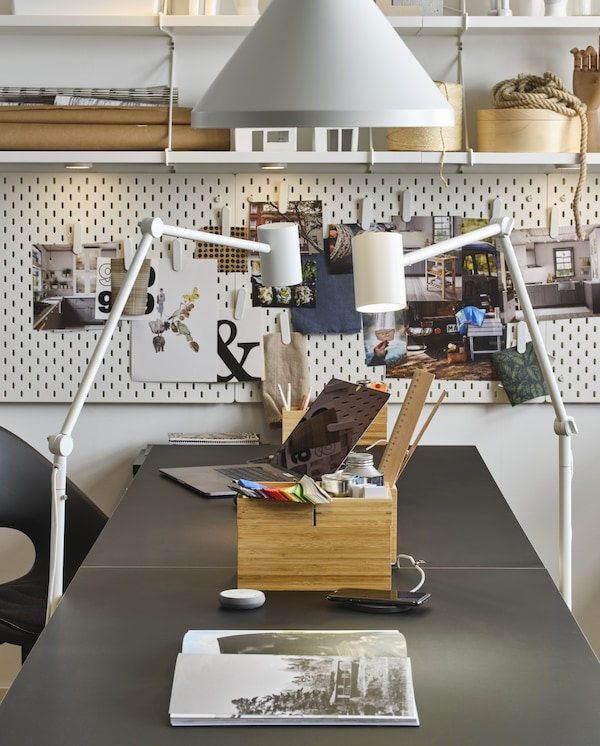 Two floor lamps and one pendant lamp in white, a black table, a laptop, a box in bamboo and shelves and pegboards in white.