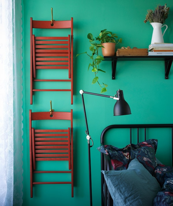 Two foldable chairs hanging on a wall beside a bed.