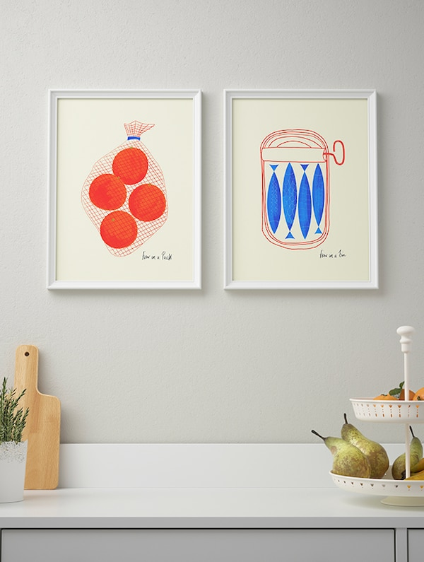 Two framed photographs of food above a kitchen countertop.