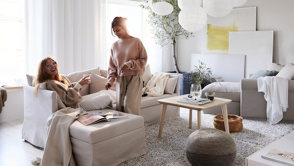Two girls in 20's laughing in neutral coloured living room setting. One woman sitting on 2-seater sofa with ottoman.
