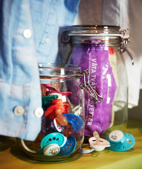 Two glass jars standing on a shelf, shirt sleeves dangling around them. One jar is filled with dummies, the other wet wipes.