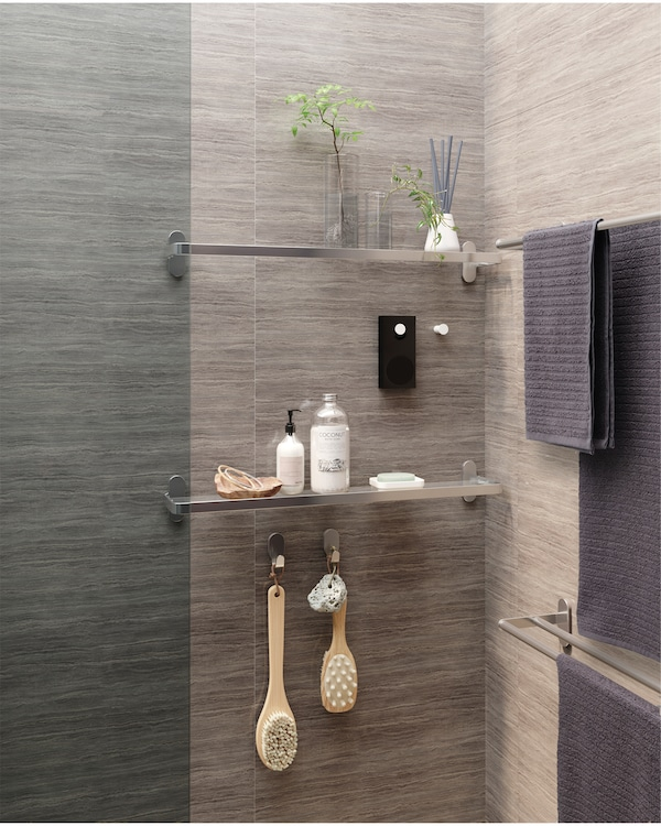 Two glass shelves are mounted on a wall and between them a white knob where a small portable Bluetooth speaker is hanging.