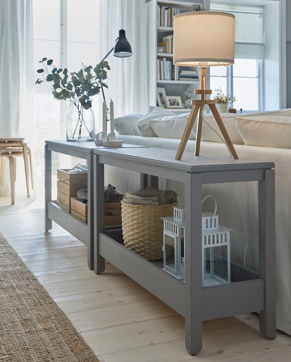 Two gray console tables are placed behind a sofa and serve as decorative room dividers. Two table lamps are placed on top.
