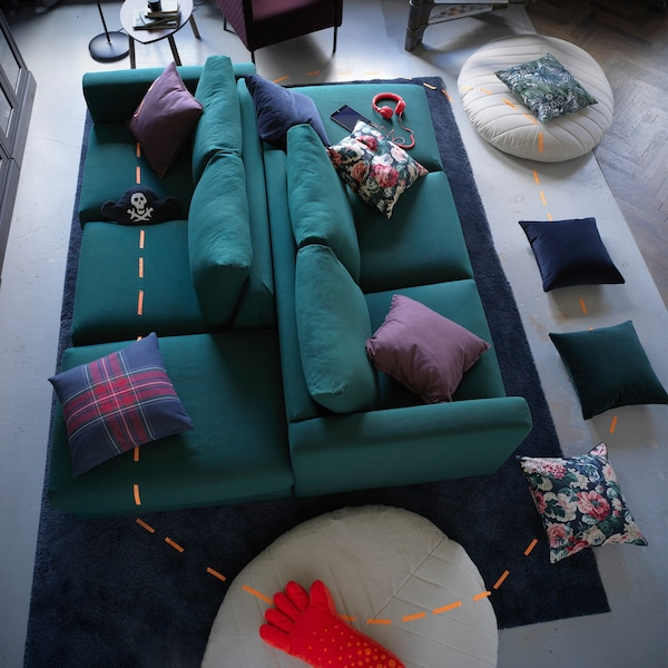 Two green VIMLE sofas back to back, with cushions and pouffes scattered around the floor and marked with a tape trail.