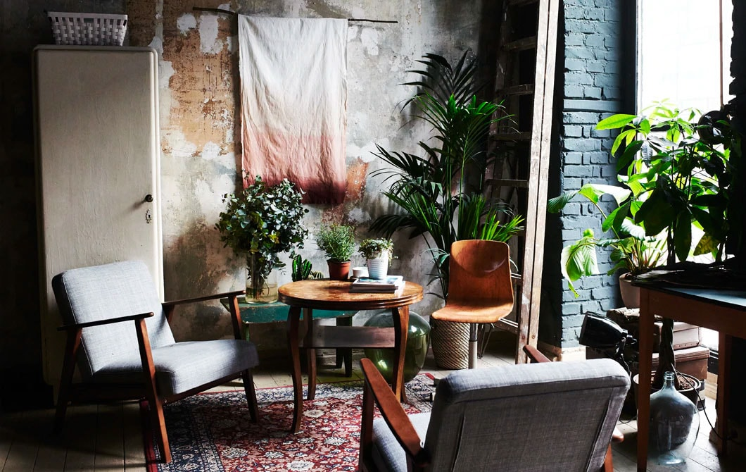 Two grey and wood armchairs positioned next to a window in a room with exposed brick walls