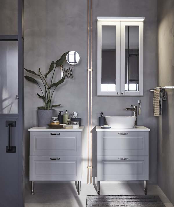 Two grey bathroom storage units, one with a sink, and a mirrored cupboard on the grey wall above.