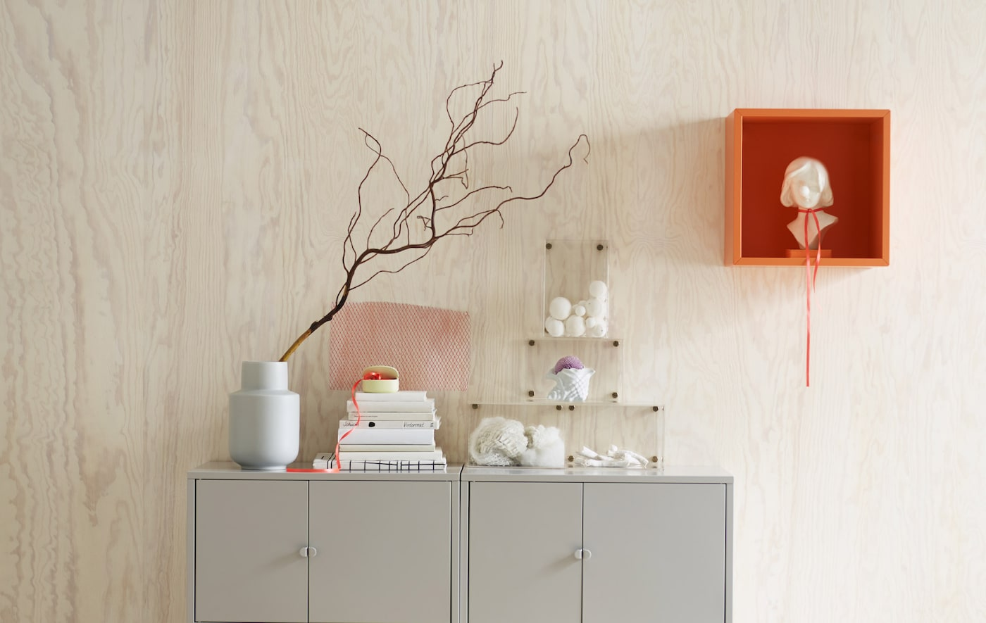 Two grey cabinets against a pine wall in fresh natural lighting, including an orange EKET wall mounted cabinet with a statue.