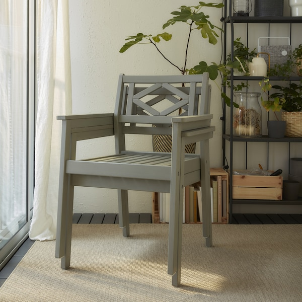 Two grey chairs with armrests are stacked. They stand on a beige rug, and a grey shelving unit with plants stands behind.