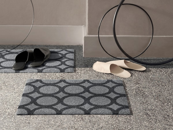 Two grey IKEA MEJLS door mats with a black circle pattern. They're made from recycled PET bottles.