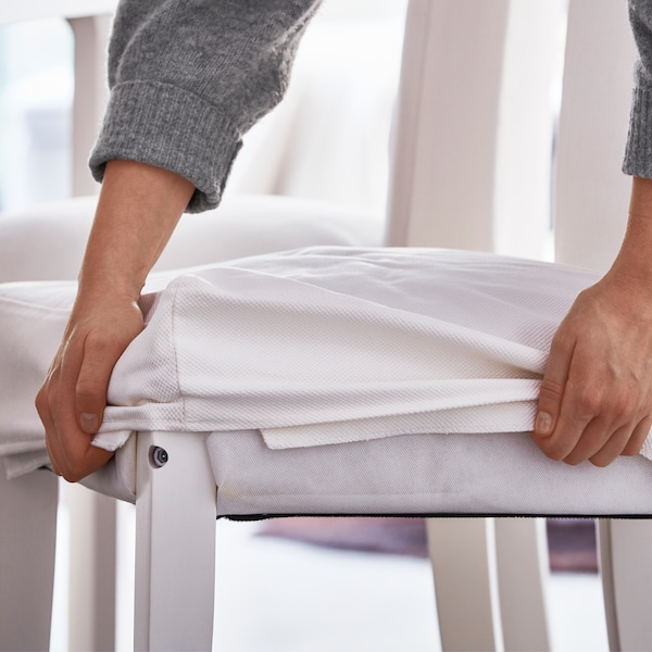 Two hands grip the edges of the white textile cover on a white, HENRIKSDAL chair that has white legs.
