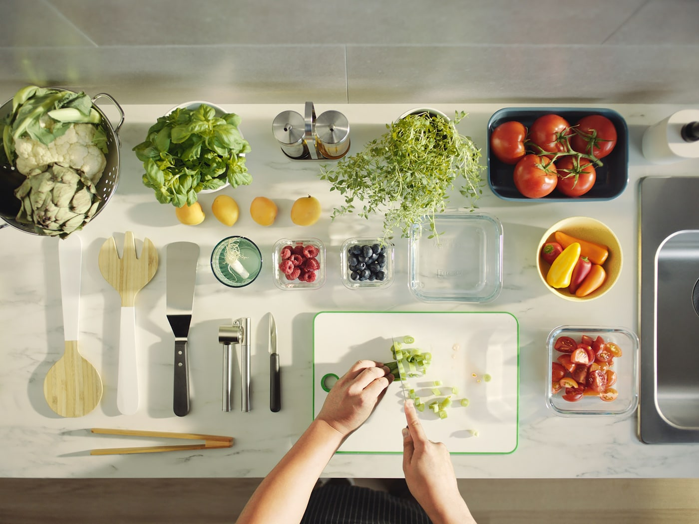 Two hands slice spring onion on a green/white MATLUST chopping board, next to kitchenware and various fruits and herbs