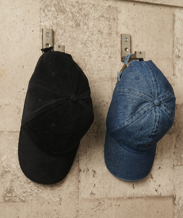 Two hats hanging on silver hooks on a brick wall.