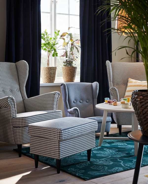 Two houndstooth-patterned STRANDMON wing chairs, and in between them stands a grey STRANDMON children's armchair.
