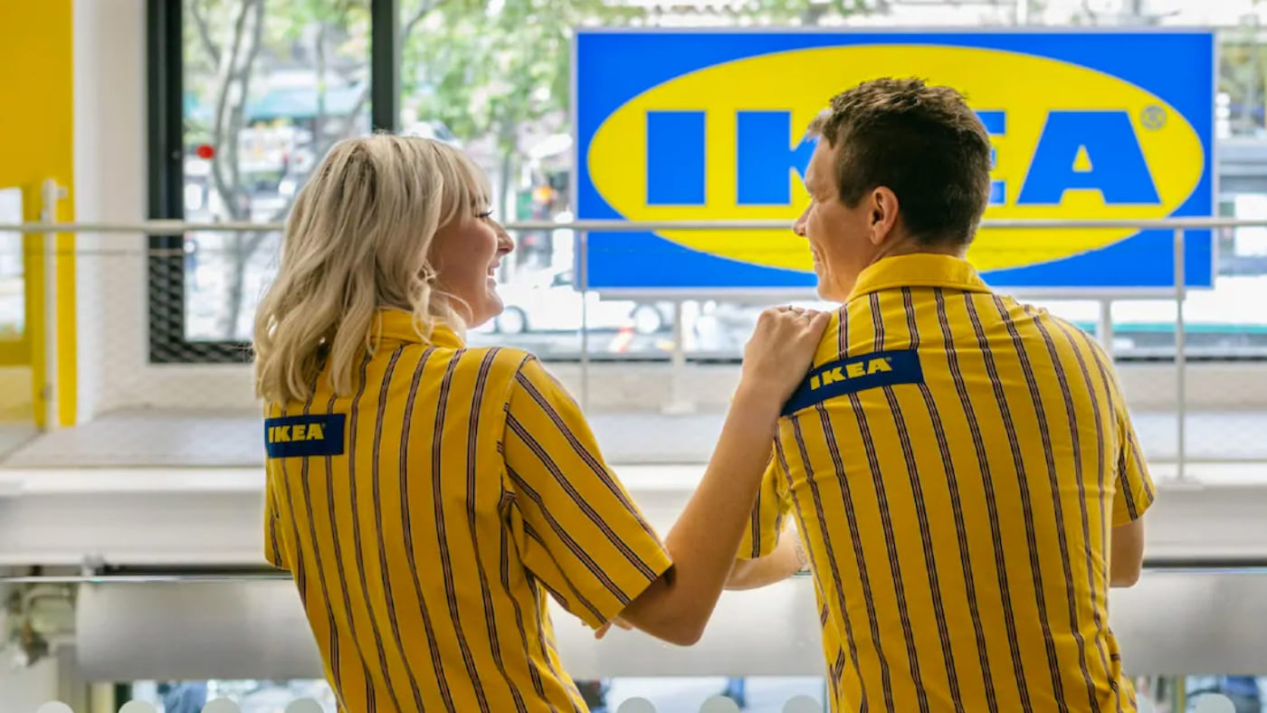 Two IKEA co-workers are standing in an IKEA store. They are both looking and smiling at each other.