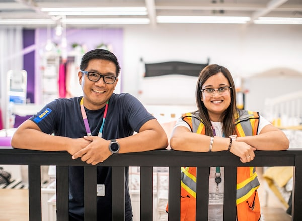 Two IKEA co-workers leaning over a wooden frame. They are both wearing lanyards and are smiling.