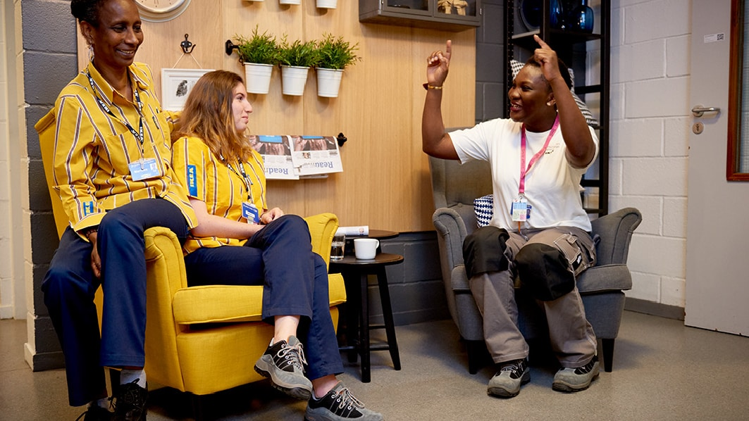Two IKEA co-workers sitting on a yellow chair, listening to another person talk as they share their values and experience.
