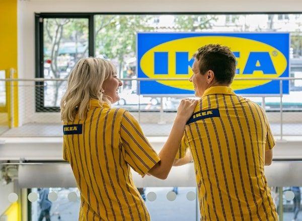 Two IKEA co-workers wearing yellow and blue IKEA t-shirts. They are standing in an IKEA store.