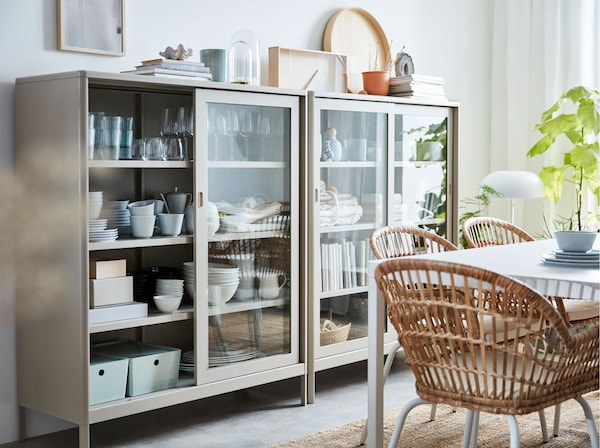 Two IKEA IDÅSEN beige cabinets with two sliding glass doors used to store tableware, books and decorative accessories.