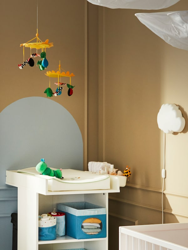 Two IKEA KLAPPA mobiles above a changing table with baby changing products, a soft toy caterpillar and a wall night light.