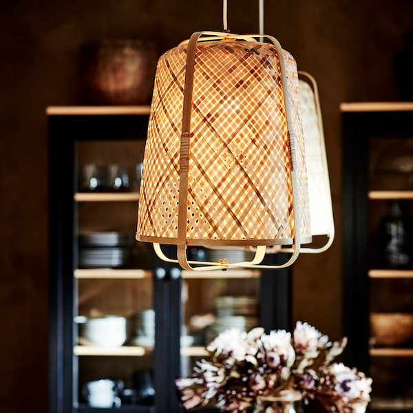 Two IKEA KNIXHULT bamboo ceiling lamps are hanging in a kitchen. There are cupboards filled with crockery in the background.