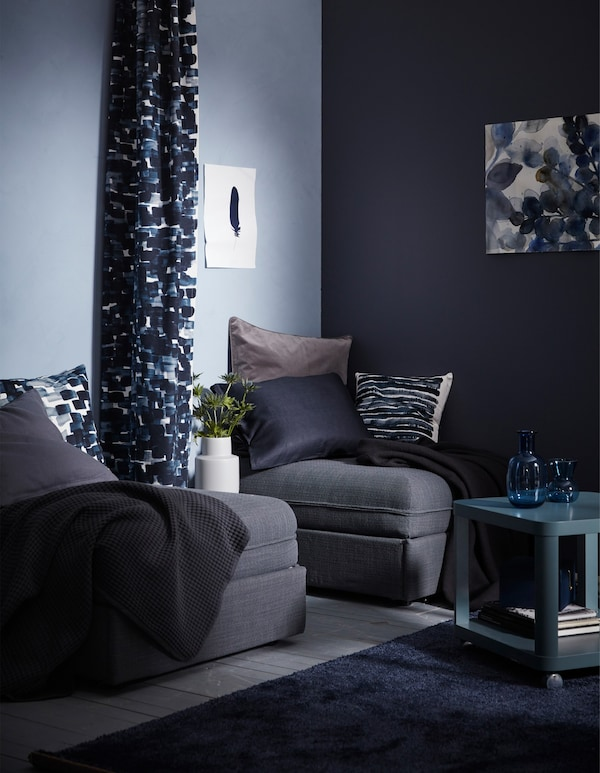 Two IKEA sofa beds in a living room with one light blue and one dark blue wall.