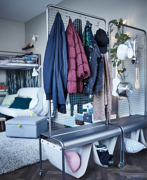 Two IKEA VEBERÖD room dividers used as rolling storage on wheels with hanging clothes and kitchen utensils.