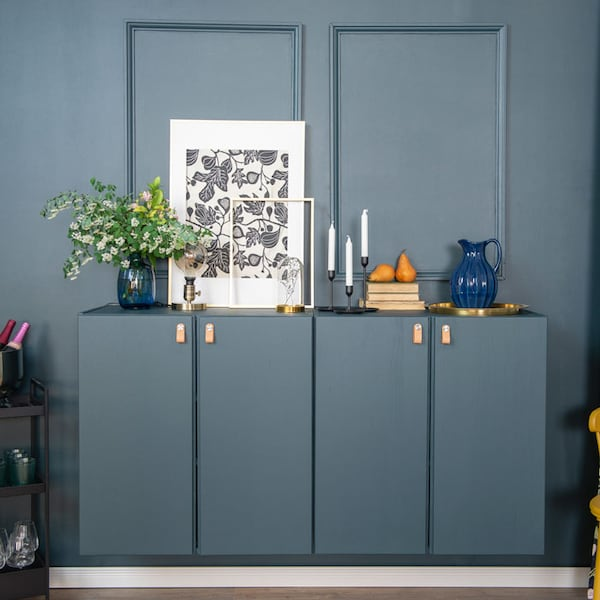 Two IVAR cabinets on a wall are painted blue and have leather handles. Several items are placed on top of the cabinets, such as candles, a picture frame, and a plant in a vase.