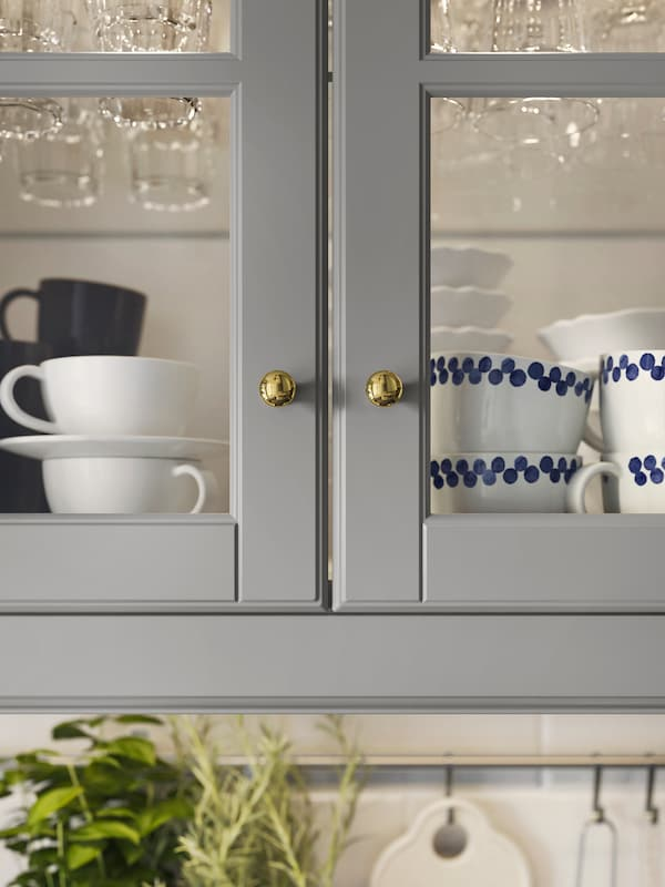 Two kitchen cabinets with glass doors and grey frames, containing a selection of coffee cups and glasses.