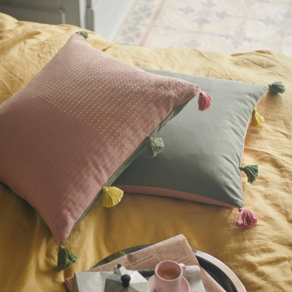 Two KLARAFINA cushion covers showing their pink and green sides with coloured tassels along the edge too.