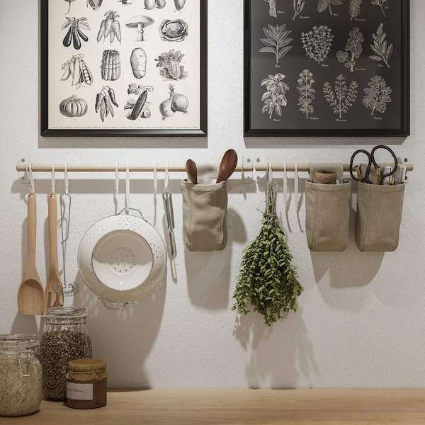 Two KNOPPÄNG frames with posters and NEREBY birch rails on a white wall, with hanging kitchen utensils and containers.