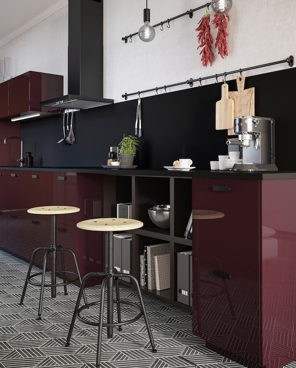 Two KULLABERG stools in pine/black stand by a kitchen countertop where a coffee machine and some mugs are close at hand.