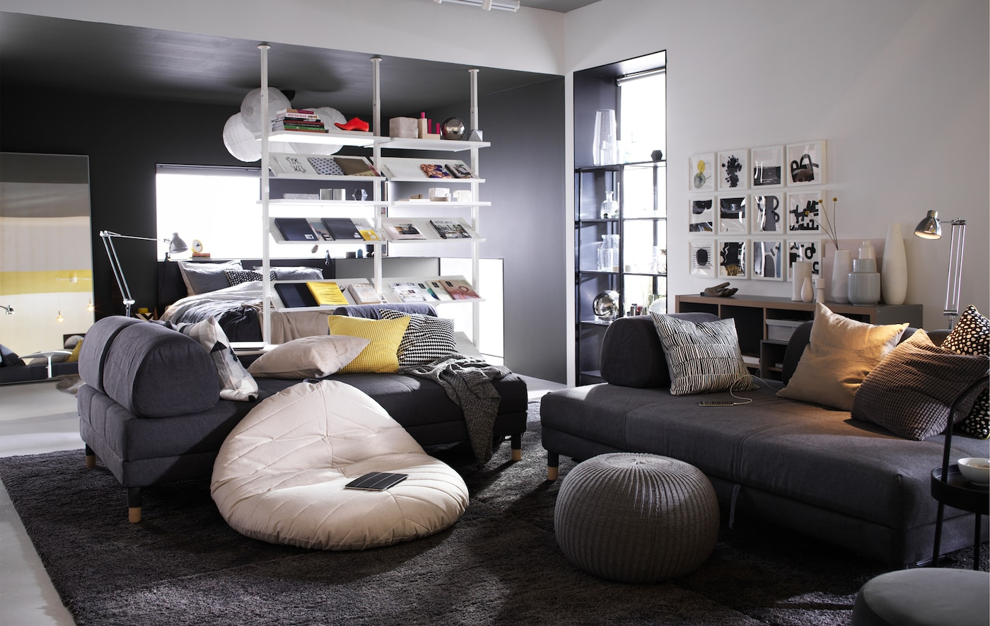 Two large dark grey sofas in a living room, with an IKEA DIHULT natural pouffe on a dark rug.