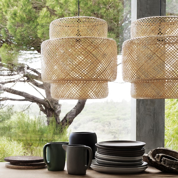 Two large SINNERLIG bamboo pendant lamps hung above a table informally set with rustic ceramic dishes.