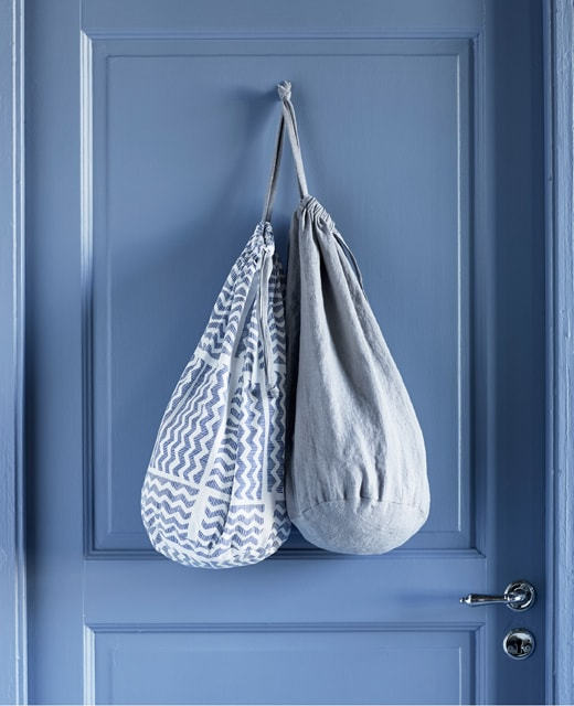 Two laundry bags with different textiles, hanging over the back of a door.