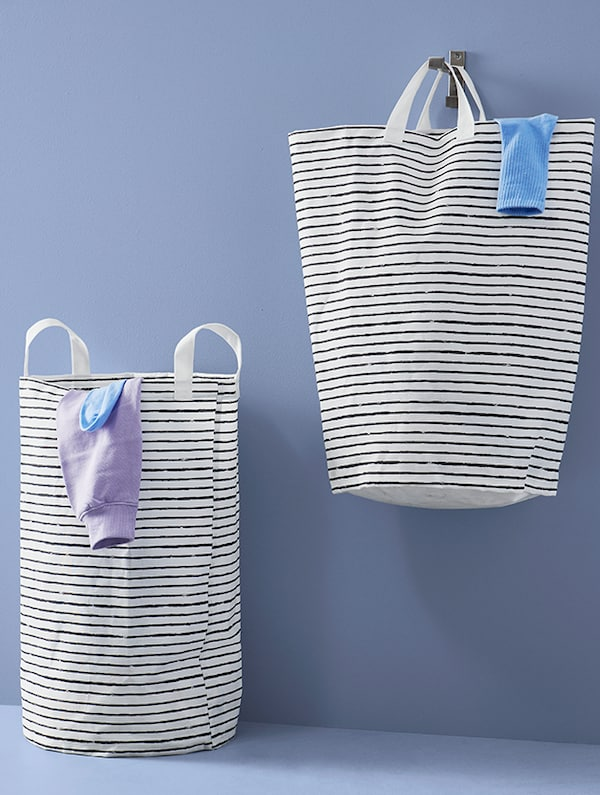 Two laundry baskets. One is sitting on the ground while the other is suspended in the air via a wall hook.
