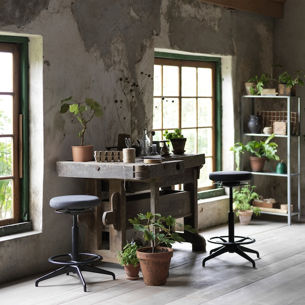 Two LIDKULLEN active sit/stand supports in dark grey placed in a gardener's workspace surrounded with plants.