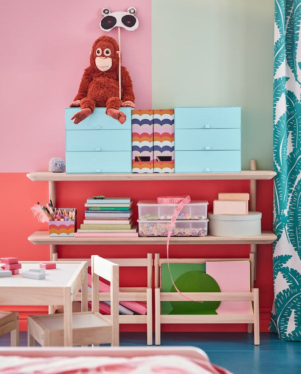 Two LISABO wall shelves in ash veneer – they store graphic, colourful storage boxes, a soft toy orangutan, books and crafts.
