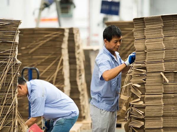 Two men sorting boxes at an IKEA supplier.