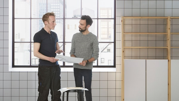 Two men standing in front of a wall with square tiling and shelving, talking to each other while holding documents.