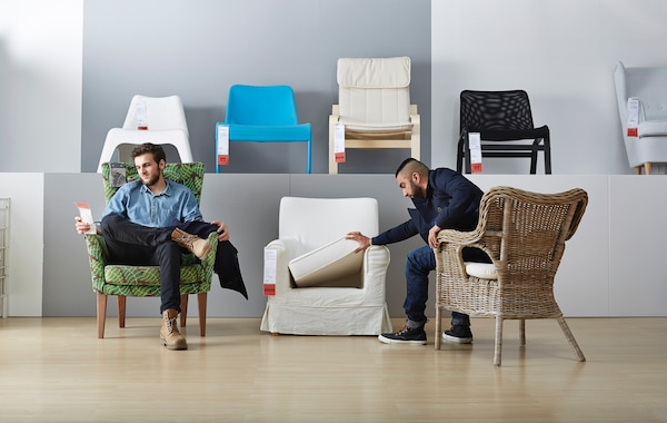 Two men trying out IKEA armchairs