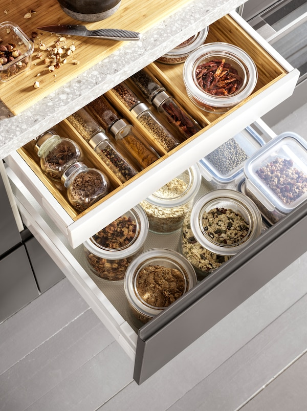 Two open kitchen drawers with grains in glass jars and spices neatly organised inside a VARIERA cutlery tray in wood.