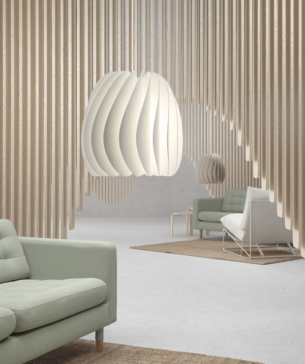 Two pendant lampshades hanging in a room with pale green sofas and wooden panelled decoration.