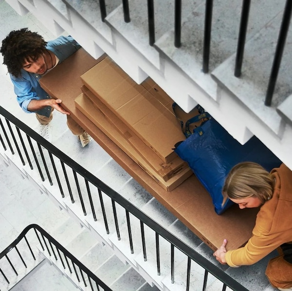 Two people carry packages up the stairs.