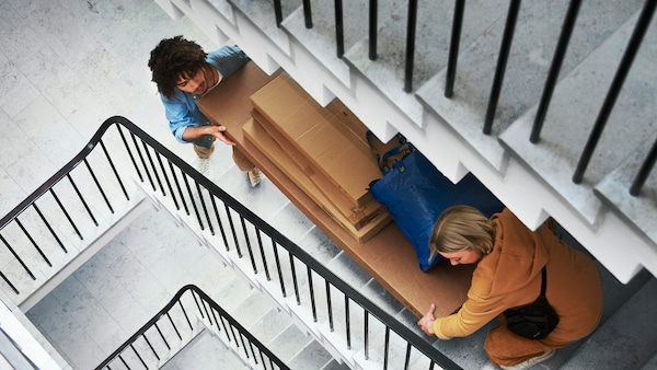 Two people carry several large IKEA flat-pack boxes and a blue IKEA bag up a flight of grey stairs in an apartment building.