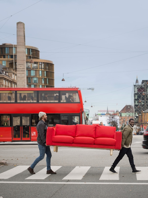 Two people carrying a red sofa across the street with a red bus and the city in the background.