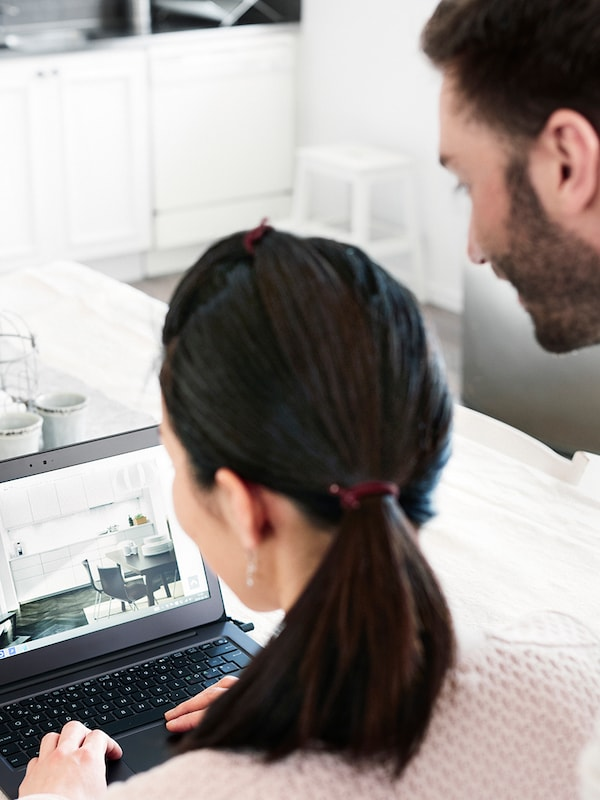 Two people looking at their laptop's screen, while getting ready for an IKEA home furnishing advice service.
