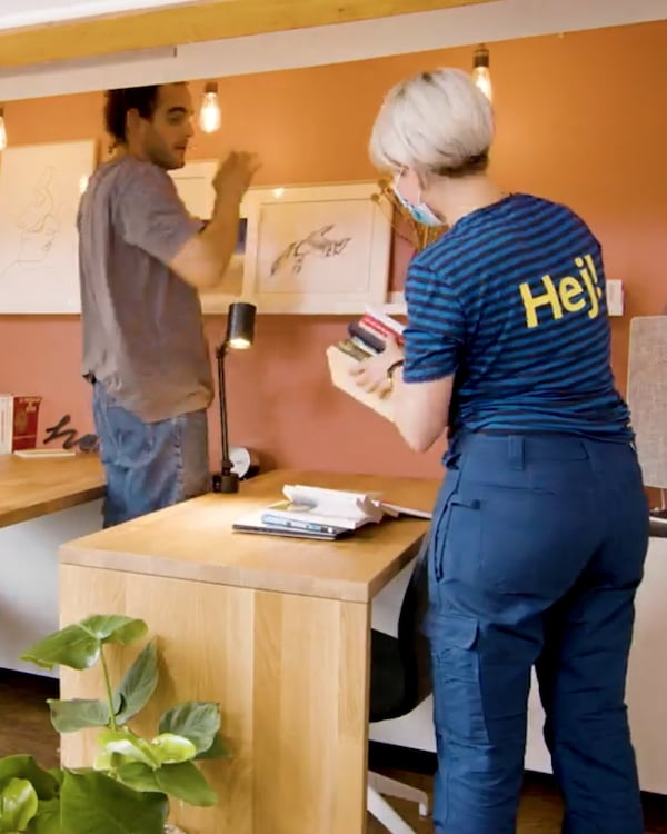 """Two people place a stack of books and a picture frame on and around a wooden desk. The woman in the foreground has blonde hair and wears a blue striped shirt with """"Hej!"""" written on the back. The man in the background has brown hair and wears a beige t - shirt."""