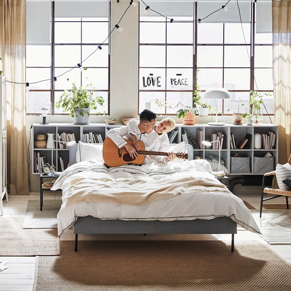 Two people playing guitar in bed in a bright bedroom with open windows.