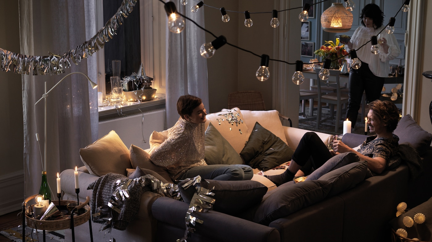 Two people sit together in two sofas that have been pushed together in the middle of a room, laughing and chatting.