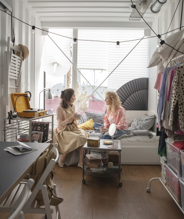Two people sitting on a daybed in a room with an open clothes rail, trolleys on wheels, and chairs stored on the walls.